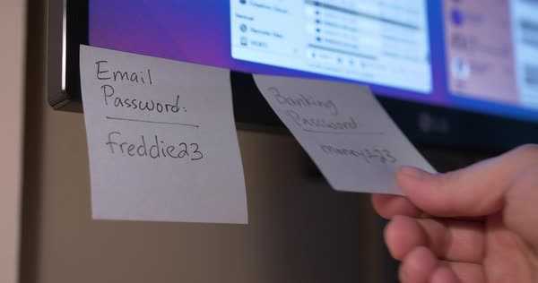 A person places Post-It password reminders on a computer monitor.  Royalty-free stock video