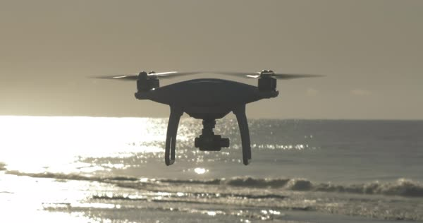 A backlit shot of a silhouetted drone or UAS flying over the ocean.  Royalty-free stock video