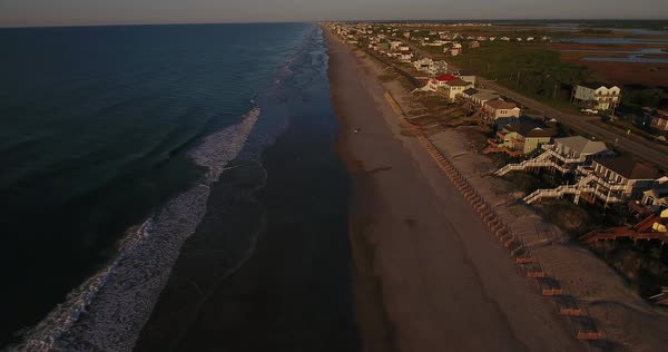 An early morning rising aerial establishing shot of the houses along Topsail Island on the Atlantic Ocean in North Carolina.  Royalty-free stock video