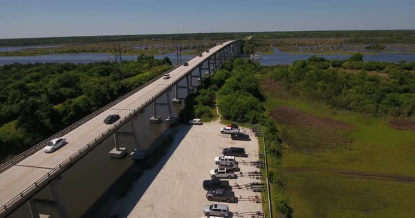 A daytime forward moving aerial establishing shot of the Topsail Island Bridge over the Intracoastal Waterway as traffic passes over top.  Royalty-free stock video