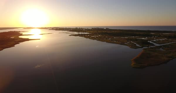 A slowly moving reverse aerial establishing shot of the sunrise over Topsail Beach, North Carolina. Royalty-free stock video