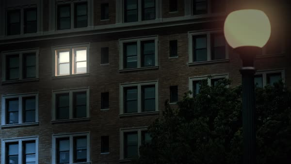 "A typical New York style apartment or office building establishing shot at night with the light from only one window on. Simulated ""day-for-night"" composite.  Royalty-free stock video"