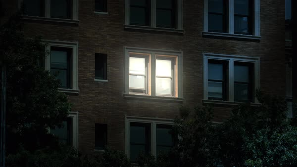 "A typical New York style apartment or office building establishing shot at night with the lights from a window turning on then off. Simulated ""day-for-night"" composite.  Royalty-free stock video"