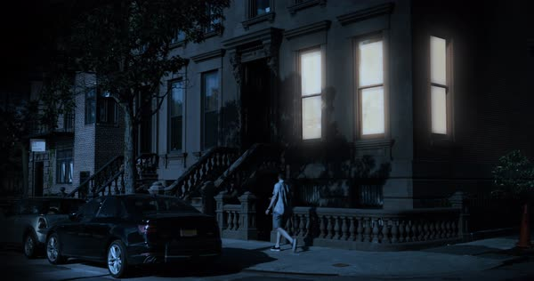 A nighttime exterior establishing shot of a typical Brooklyn brownstone residential home on a street corner as a man walks by.   Royalty-free stock video