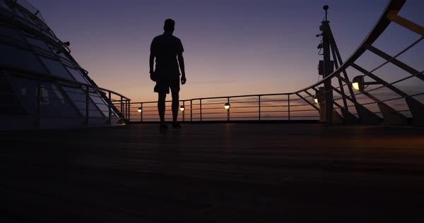 A silhouetted man walks on the deck of a large cruise ship at sunset.  Royalty-free stock video