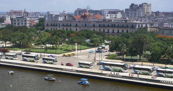 A slowly moving aerial dolly establishing shot of traffic and buildings on the Avenida del Puerto in downtown Havana, Cuba.   Royalty-free stock video