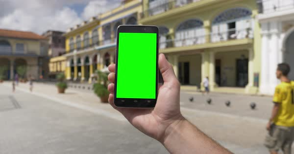 Holding a green screen smartphone in portrait mode in Havana's Old Town Square Plaza Royalty-free stock video