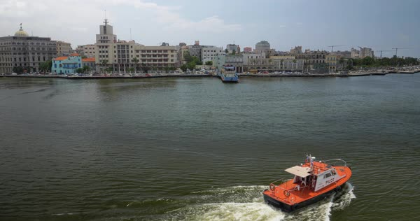 A small tug pilot boat travels in Havana Port Bay with the old town skyline in the distance.  Royalty-free stock video