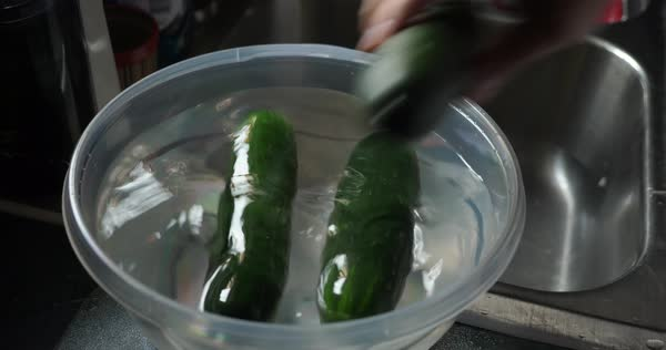 A person places three cucumbers into a bowl of water on a kitchen sink. Cleaning food, healthy lifestyle situation.   Royalty-free stock video