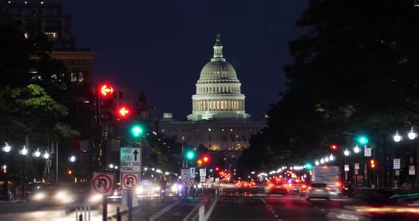 A night timelapse view of traffic activity on Pennsylvania Avenue in Washington, D.C. with the Capitol Dome in the distance.  Royalty-free stock video