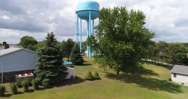 A daytime rising aerial establishing shot of a typical Pennsylvania residential neighborhood with a large water tower in the foreground.   Royalty-free stock video