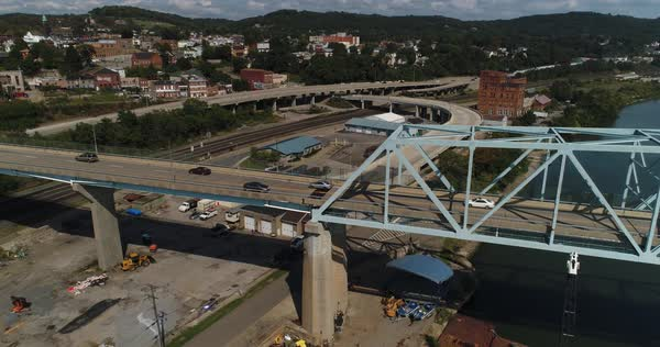 A high angle rising aerial establishing shot of traffic passing on the Rochester Monaca Bridge over the Ohio River in Western Pennsylvania.   Royalty-free stock video