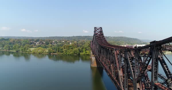 A reverse high angle aerial establishing shot of a railroad bridge over the Ohio River in Pennsylvania. The small town of Beaver is in the distance.  Royalty-free stock video