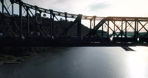 A silhouetted aerial shot of a cargo train traveling over a railroad bridge spanning the Ohio River.   Royalty-free stock video