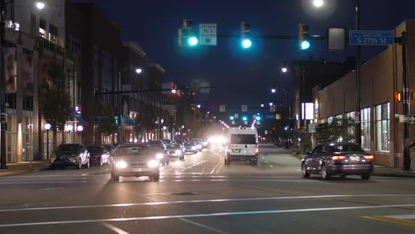 A nighttime establishing shot of traffic and buildings along East Carson Street in Pittsburgh's South Side district.   Royalty-free stock video