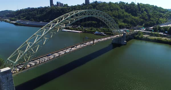 A slow, cinematic rising up dolly establishing shot of Pittsburgh's West End Bridge over the Ohio River.   Royalty-free stock video