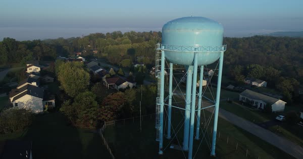 A slow forward aerial view of a tall blue water tower in a typical Pennsylvania neighborhood.  Royalty-free stock video