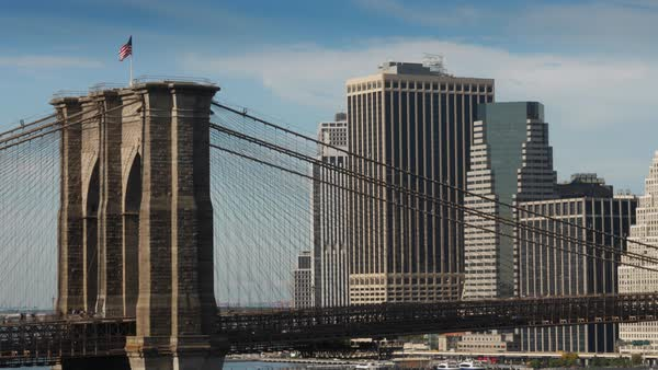 A long shot view of the famous Brooklyn Bridge over the East River with the financial district skyline in the distance.   Royalty-free stock video