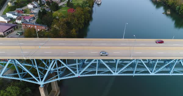 A daytime high angle aerial profile establishing shot of light traffic on the Rt 40 Market Street Bridge over the Monongahela River in Brownsville, PA - a Pittsburgh suburb.   Royalty-free stock video