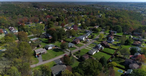 A daytime forward aerial establishing shot of a typical western Pennsylvania residential neighborhood in the early autumn. Royalty-free stock video