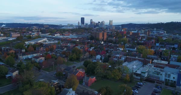An evening reverse aerial establishing shot from a residential neighborhood with the Pittsburgh skyline in the distance. Royalty-free stock video