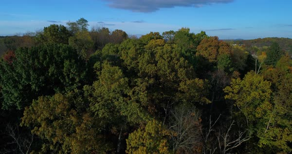 A rising aerial establishing shot revealing the landscape of a typical Western Pennsylvania valley and residential neighborhood in Autumn. Royalty-free stock video