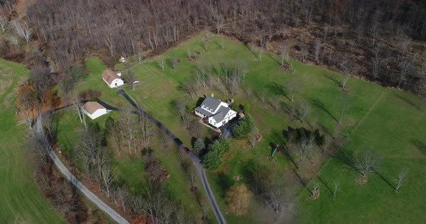 A high angle aerial flyover of a typical Western Pennsylvania farmhouse in the late Autumn.  Royalty-free stock video