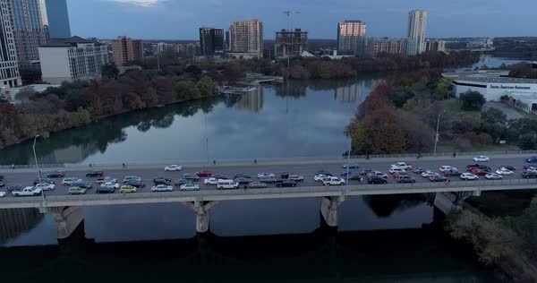 A slow aerial tilt down of traffic on the Congress Avenue Bridge over the Colorado River in Austin, Texas on an early Winter evening.   Royalty-free stock video