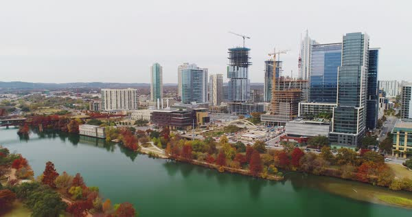 A slow forward aerial establishing shot of Austin, Texas and the Colorado River on an overcast day.   Royalty-free stock video
