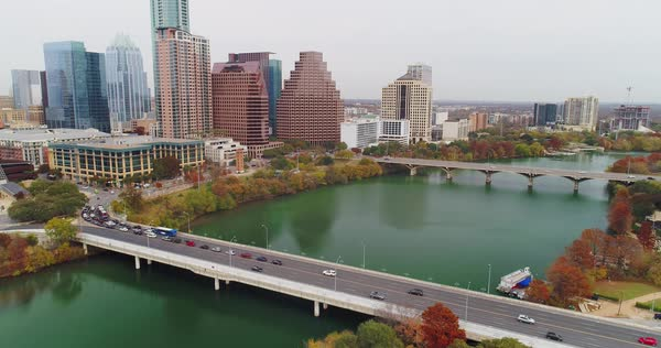 A tilt down aerial establishing shot of the S 1st Street Bridge over the Colorado River in downtown Austin, Texas on an overcast Winter day.   Royalty-free stock video