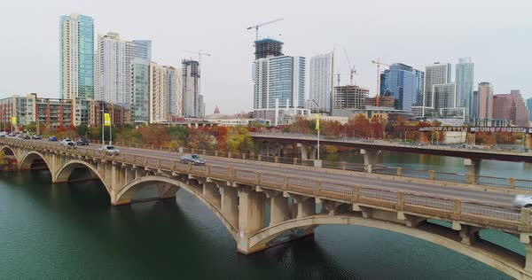 A daytime overcast aerial reverse view of traffic flowing over the S Lamar Boulevard bridge in downtown Austin, Texas on an overcast winter's day.   Royalty-free stock video