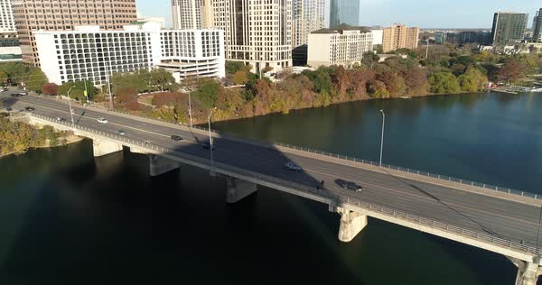 A slow reverse aerial view of traffic flowing over the S Congress Avenue Bridge over the Colorado River in downtown Austin, Texas on an early autumn evening.   Royalty-free stock video