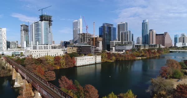 A slow reverse aerial establishing shot of the Austin, Texas city skyline on a sunny late Autumn day. Railroad bridge and Colorado River in the foreground.   Royalty-free stock video