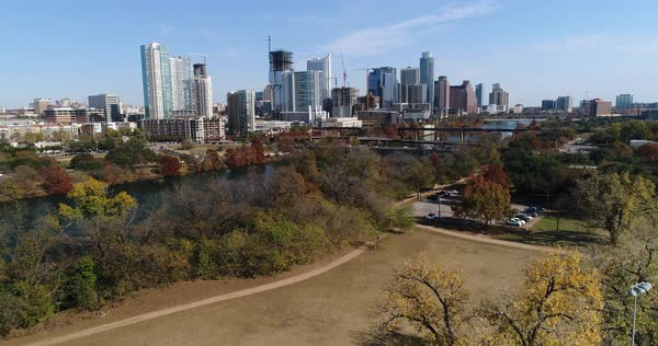 A slow forward aerial establishing shot (DX) of the Austin city skyline as seen from Butler Shores at Town Lake Metro Park on a late sunny Autumn day.   Royalty-free stock video