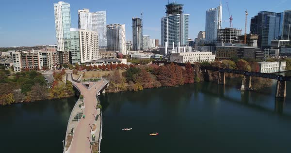 A slow rising aerial establishing shot (DX) of the Austin city skyline with the Pfluger Pedestrian Bridge and kayakers in the Colorado River in the foreground on a late sunny Autumn day.   Royalty-free stock video