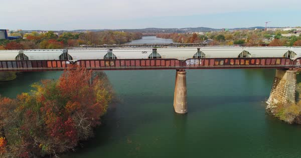AUSTIN, TX - Circa December, 2017 - A rising aerial flyover of a train traveling on a bridge over the Colorado River in Austin, Texas revealing he Pfluger Pedestrian Bridge in the distance.   Royalty-free stock video