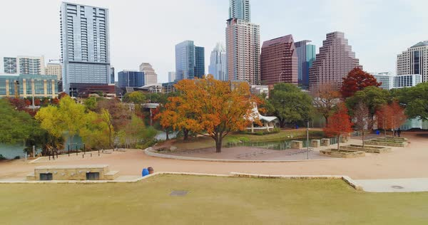 A dramatic rising aerial establishing shot of the Texas, Austin skyline with the Colorado River in the foreground. Late Autumn day with foliage trees.   Royalty-free stock video