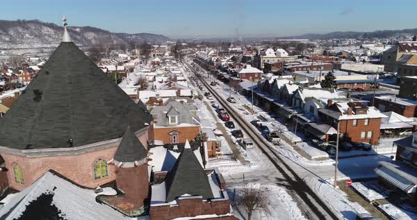 A daytime winter slow orbit aerial establishing shot of a quiet small town's residential neighborhood after a fresh snowfall. Pittsburgh suburbs.  Royalty-free stock video