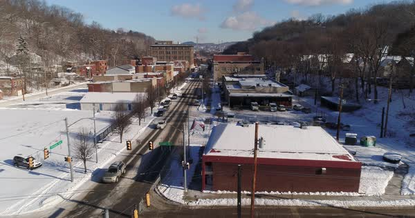 A slow forward aerial establishing shot of the Aliquippa, PA business district after a snowfall. Pittsburgh suburb.   Royalty-free stock video