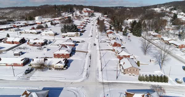 A slow reverse winter aerial establishing shot of cars traveling over snow covered roads in a rust belt residential neighborhood. Pittsburgh suburbs.   Royalty-free stock video