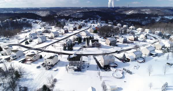 A slow rising forward winter aerial establishing shot of snow covered roads and homes in a rust belt upscale residential neighborhood. Factory smokestacks in the distance. Pittsburgh suburbs.  Royalty-free stock video