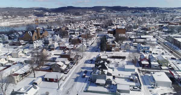 A slow forward winter aerial establishing shot of snow covered roads and homes in a rust belt residential neighborhood. Rochester and Ohio River in the distance. Pittsburgh suburbs.  Royalty-free stock video