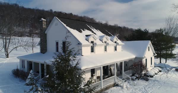 A slow aerial flyover establishing shot of a typical snow-covered Pennsylvania farmhouse in Winter.  Royalty-free stock video