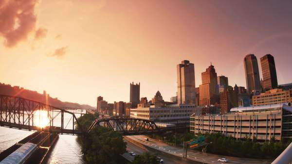 An establishing shot of the skyline of Pittsburgh at dusk as a coal barge passes by. Royalty-free stock video
