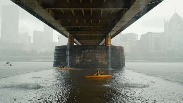 PITTSBURGH, PA - Circa May, 2015 - Kayakers desperately race to find cover under the Andy Warhol Bridge during an unexpected thunderstorm over Pittsburgh's Allegheny River. Royalty-free stock video