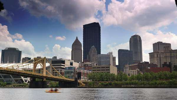 A timelapse establishing shot of the city of Pittsburgh, PA as kayakers paddle on the Allegheny River. Royalty-free stock video
