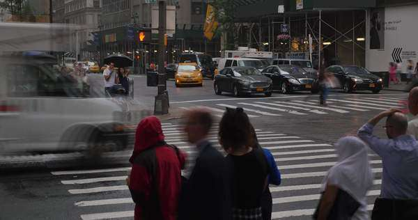 NEW YORK CITY, June, 2015 - Timelapse shot of pedestrians with umbrellas try to avoid raindrops on the streets of New York City. Royalty-free stock video