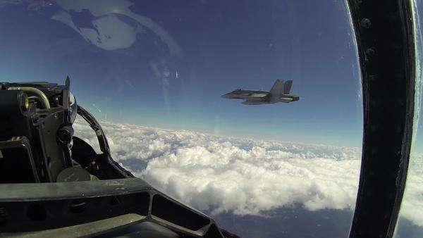 POV from backseat of F18 fighter plane flying and doing turning maneuvers through clouds as other F18 fighter plane holds position beside, getting slightly closer. Royalty-free stock video