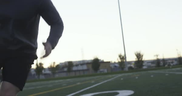 Hand-held shot of a young man running wind sprints on a football field outdoors Royalty-free stock video