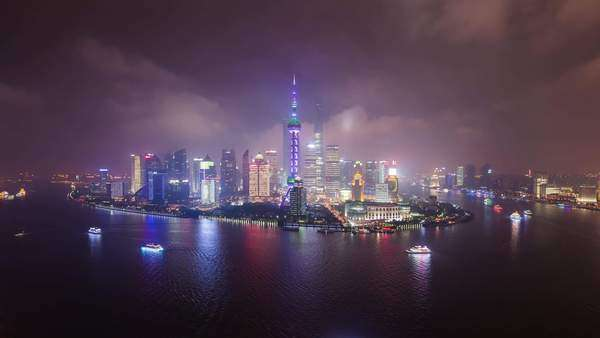 Shanghai Pudong wide static shot with clouds, boats at night. Vibrant cityscape footage. Taken from The Bund Rights-managed stock video